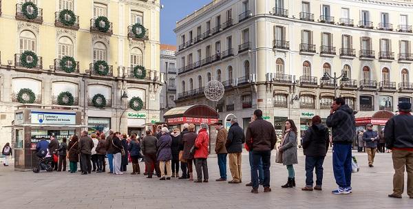 Una fila de personas ante la administración de lotería de la Puerta del Sol de Madrid. / Barcex.