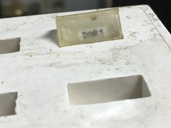 Una de las muestras del laboratorio incrustada en una resina y acompañada de su referencia. / UCM.