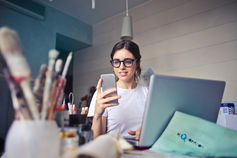 Chica consultando PC y móvil