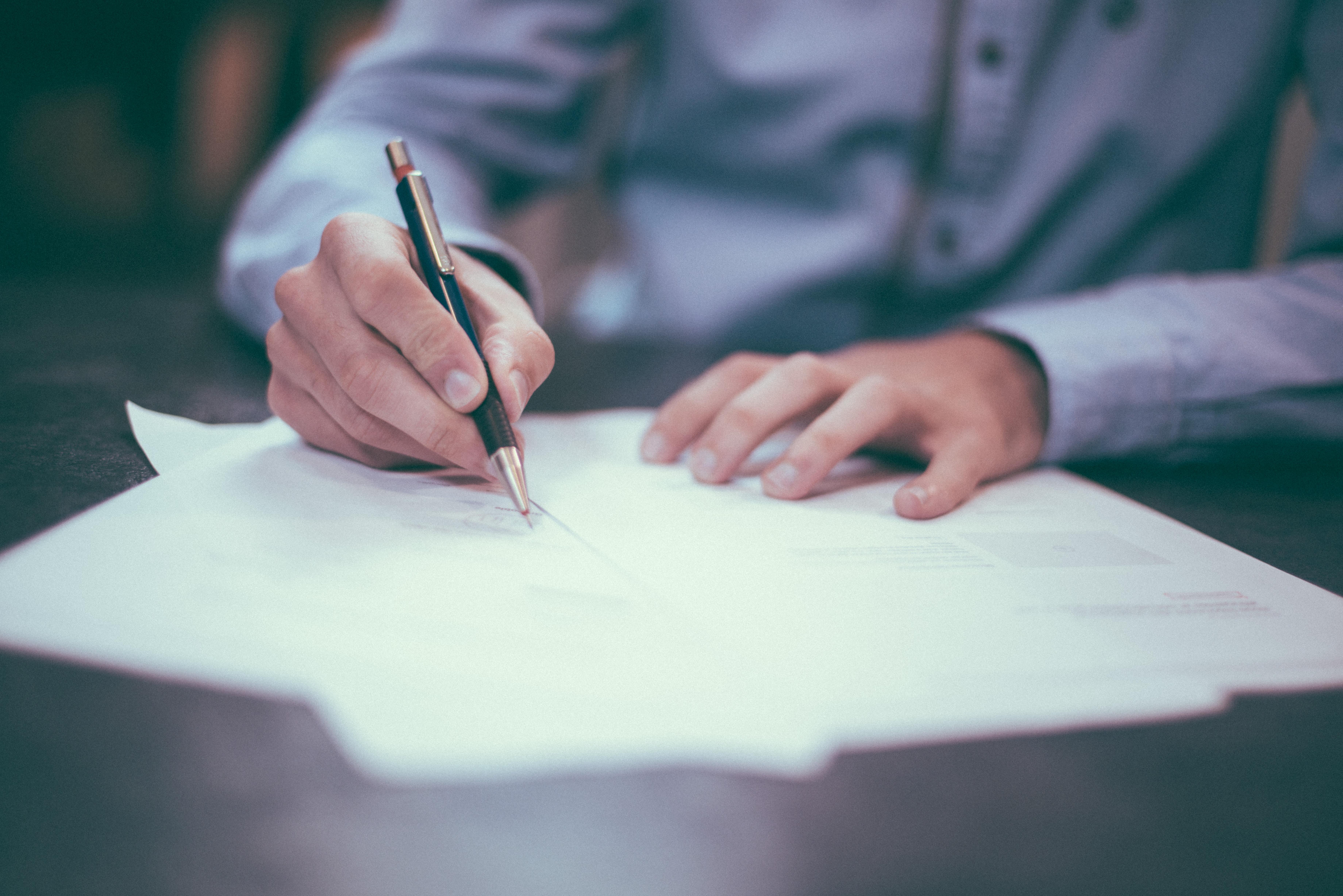 foto de alguien firmando un documento
