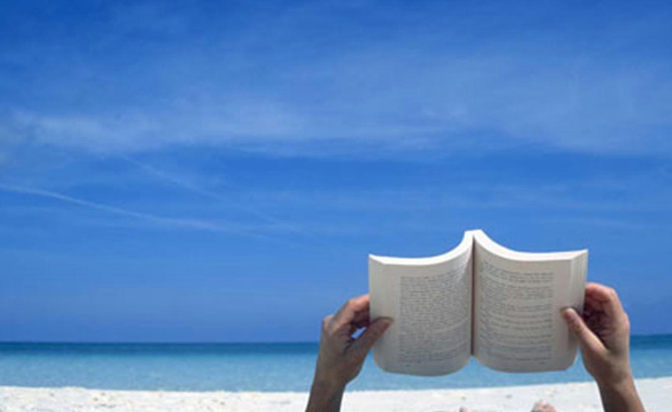 foto de alguien leyendo un libro en la playa